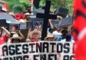 Fotoğrafta Aguan'dan gelen köylü protestocular Tegucigalpa yaptıkları bir yürüyüşte üzerinde toprak çatışmalarında öldürülen kişilerin fotoğrafları olan tabutları taşırken görülüyor.