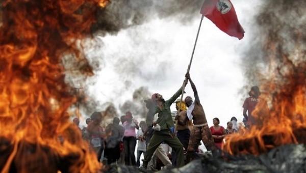 Brezilya Topraksız İşçiler Hareketi ya da MST üyeleri Brezilya karayolu üzerinde lastik yakarak bayraklarını dalgalandırıyorlar. | Fotoğraf: Reuters