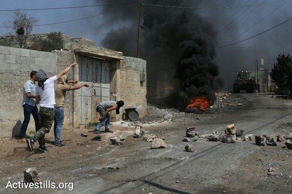 Kafr Qaddum'daki haftalık protestolar sırasında atılan taşlar ve ateşe verilen lastikler. Ağustos, 28, 2016 (Ören Ziv / Activestills.org)